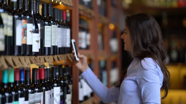beautiful young woman using a wine application on her smartphone to look at the properties of the wine - liquor store stock videos and b-roll footage