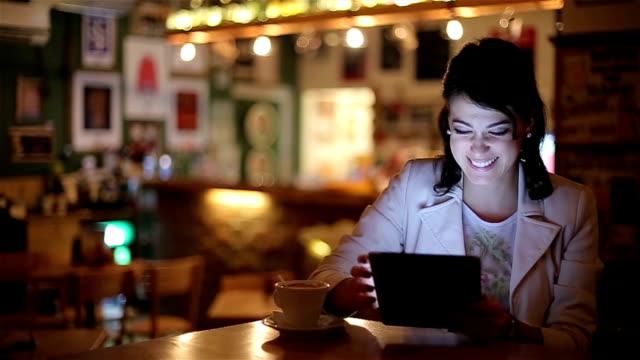 vidéos et rushes de belle jeune femme à l'aide de tablette numérique dans le café et discuter avec des amis - montre