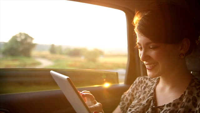 beautiful young woman using digital tablet in the back seat of the car - car interior stock videos & royalty-free footage