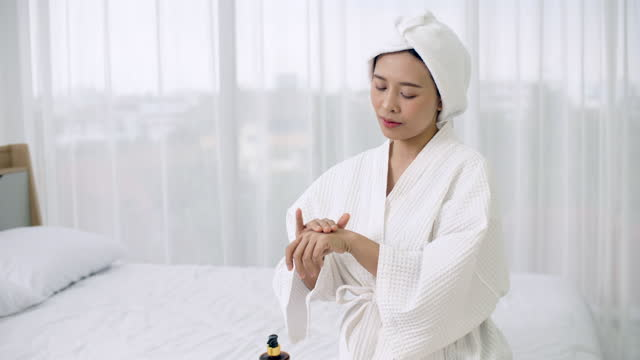 beautiful young woman using hand applying moisturizer, body care concept. - joint body part stock videos & royalty-free footage
