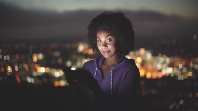 beautiful young woman using her phone at night outdoors - endast unga kvinnor bildbanksvideor och videomaterial från bakom kulisserna