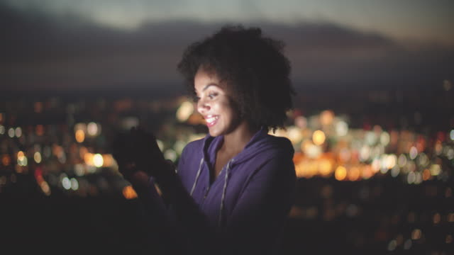 beautiful young woman using her phone at night outdoors - afro hairstyle stock videos & royalty-free footage