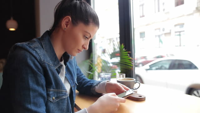 Beautiful young woman using smart phone in the coffee shop.