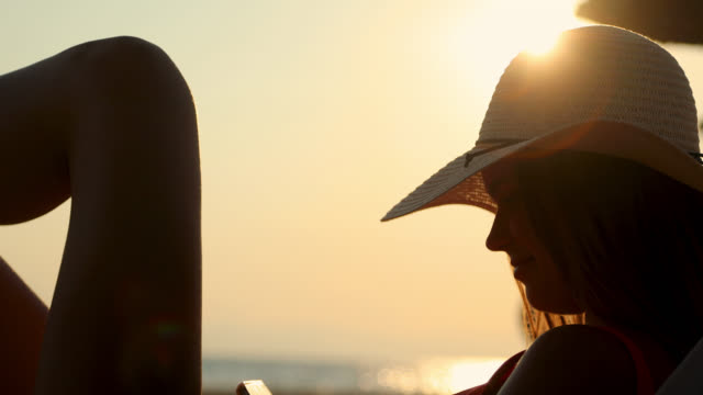 vídeos y material grabado en eventos de stock de hermosa mujer joven usando teléfono inteligente mientras se acuesta en la playa durante la hermosa puesta de sol. relajación en las vacaciones de verano - sólo mujeres jóvenes