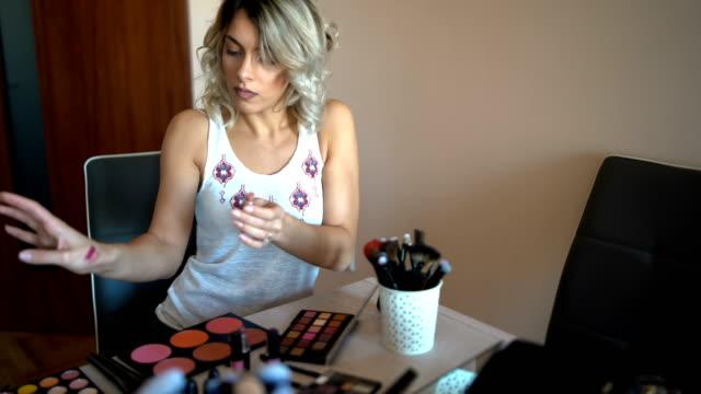 美しい若い女性が化粧品について vlogging - フェイスブラシ点の映像素材/bロール