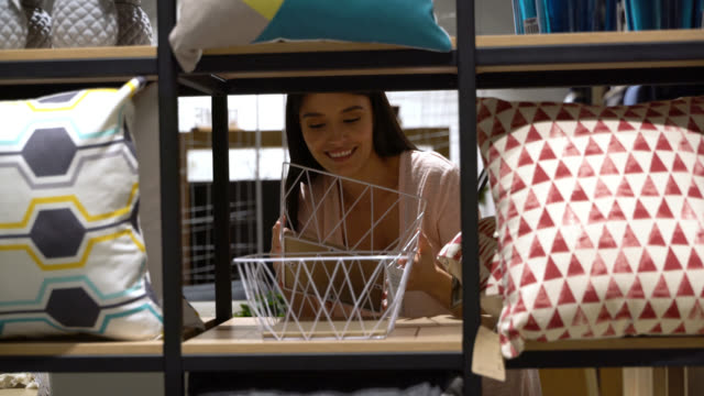 beautiful young woman walking at a furniture store and grabbing a basket from the retail display - home decor stock videos & royalty-free footage
