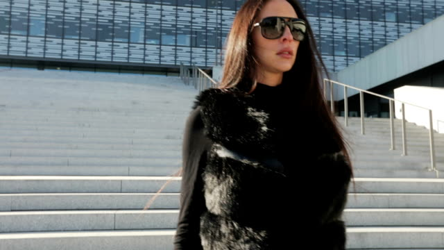 beautiful young woman walking on city street - sunglasses stock videos & royalty-free footage