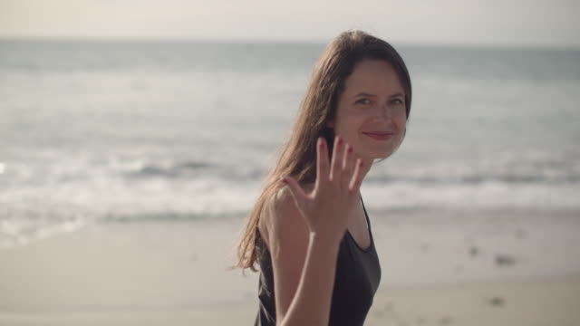 beautiful young woman walking on the beach - waving gesture stock videos & royalty-free footage