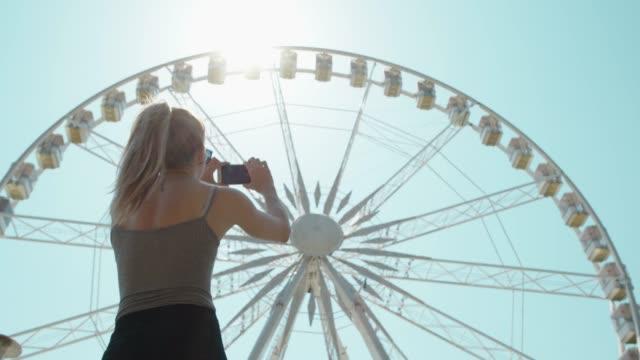 Schöne junge Frau geht vor Riesenrad und ein Foto