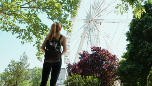 beautiful young woman walks in front off ferris wheel - budapest stock videos & royalty-free footage