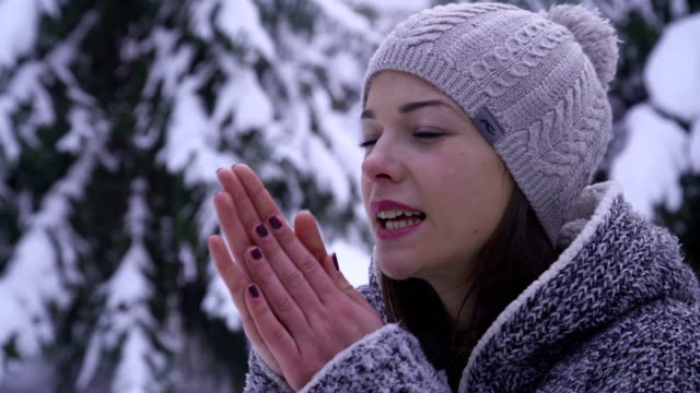 vídeos de stock e filmes b-roll de beautiful young  woman warming her hands on the snow - frio