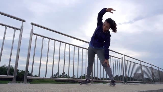 vídeos y material grabado en eventos de stock de hermosa joven calentando antes de hacer ejercicio y trotar - corredora de footing