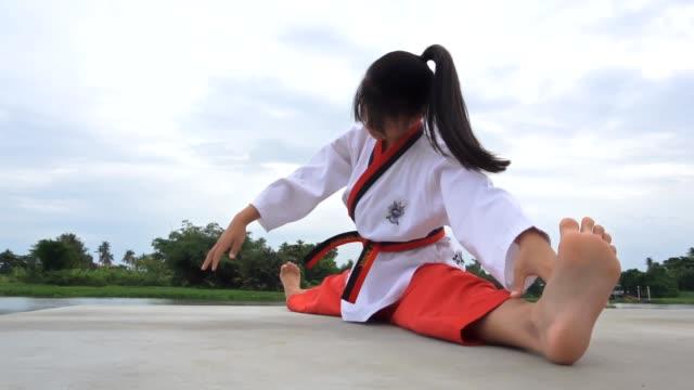 beautiful young woman warming up before exercising - taekwondo stock videos & royalty-free footage