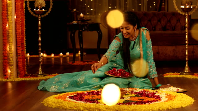 MS Beautiful young woman wearing traditional clothing making rangoli with flowers during diwali festival / Delhi, India