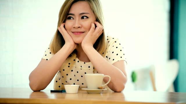 Belle jeune femme avec une tasse de café sur un café