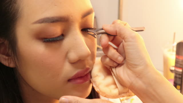 beautiful young woman with eyelash extension. woman eye with long eyelashes.close-up of a beautiful asian woman on eyelash extension procedure. - eyelash stock videos & royalty-free footage