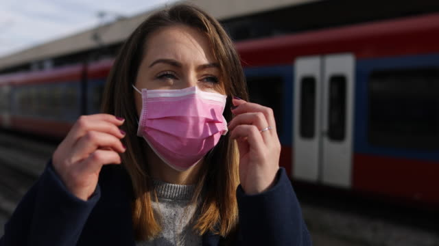 beautiful young woman with face mask on train station - train vehicle stock videos & royalty-free footage