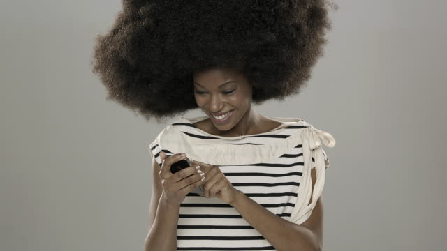 beautiful young woman with large hair texting on her phone happily