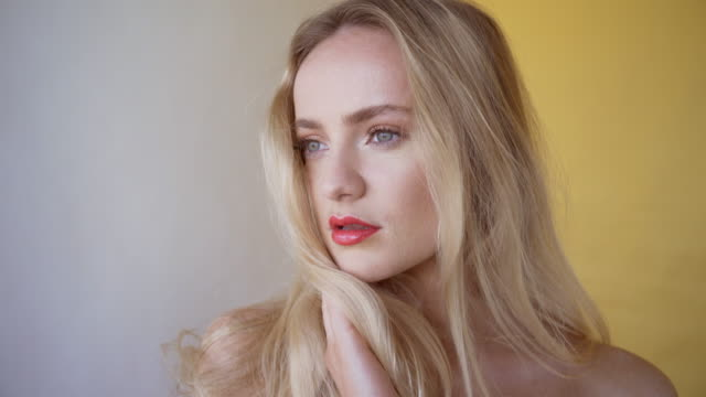 a beautiful young woman with long blond hair. with clear sharp skin and movie star make-up. - sharp stock videos and b-roll footage