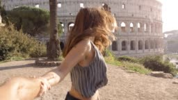 Beautiful young woman with long hair lead boyfriend by the hand towards colosseum in rome at sunset come with me attractive happy couple
