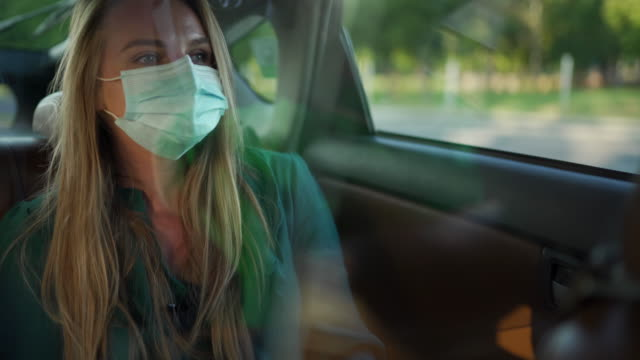 beautiful young woman with protective face mask, on back seat of crowdsourced taxi - taxi stock videos & royalty-free footage