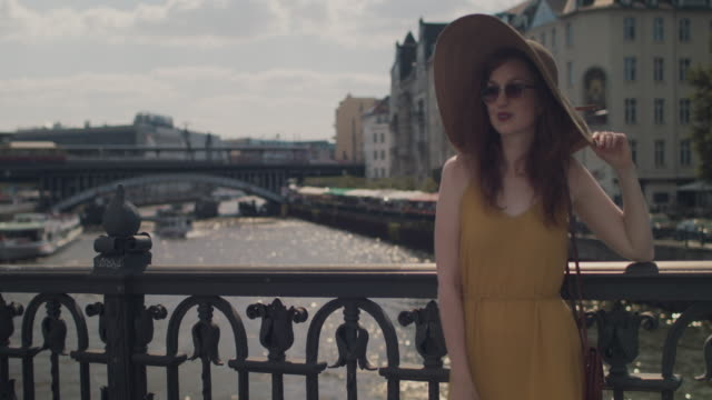 beautiful young woman with red hair and sun hat standing on bridge, enjoying sunshine in berlin, germany on a sunny day. - sun hat stock videos & royalty-free footage