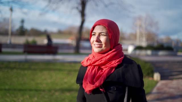 vídeos y material grabado en eventos de stock de hermosa joven con hiyab rojo disfruta de un paseo por el parque público - distante
