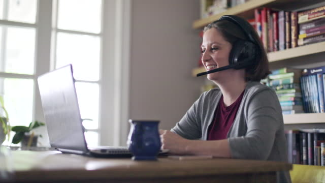 beautiful young woman working from home with headset - headset stock videos & royalty-free footage