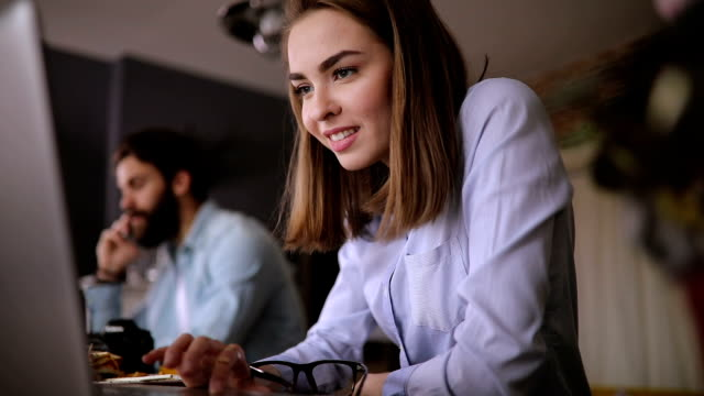 beautiful young woman working in office with her colleague - two people stock videos & royalty-free footage