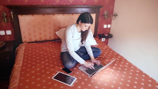 Belle jeune femme travaillant dans la chambre d'hôtel.