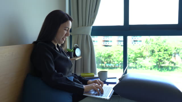 beautiful young woman working with laptop on bed - only young women stock videos & royalty-free footage