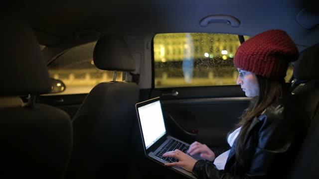 Vacker ung kvinna skriva e-postmeddelanden i baksidan av bilen.