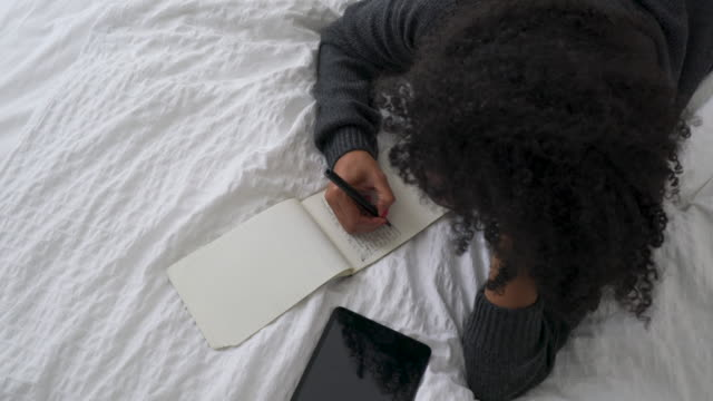 beautiful young woman writing in bed - diary stock videos & royalty-free footage