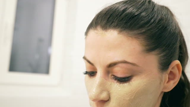 beautiful young women applying facial mask. - scrubbing stock videos & royalty-free footage
