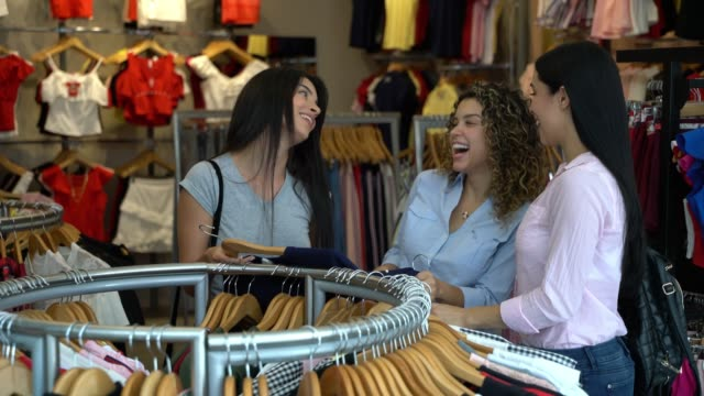 beautiful young women at a clothing store looking at different choices while laughing - female friendship stock videos & royalty-free footage