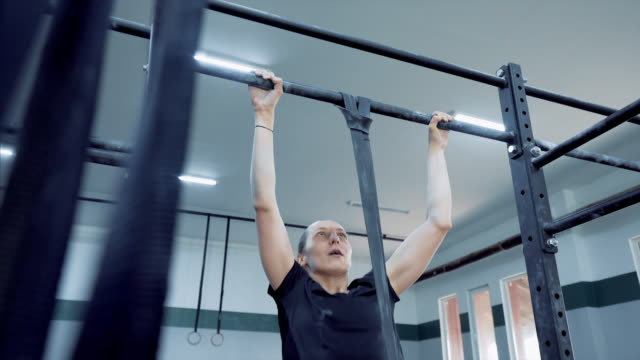 beautiful young women doing pull-ups in gym. - pull ups stock videos & royalty-free footage