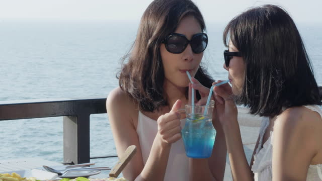 Beautiful young women drinking cocktails.Romantic couple women enjoying sun, sunshine, romance and love by the sea. Couple on summer vacation travel holiday.LGBT concept.LGBT Vacation