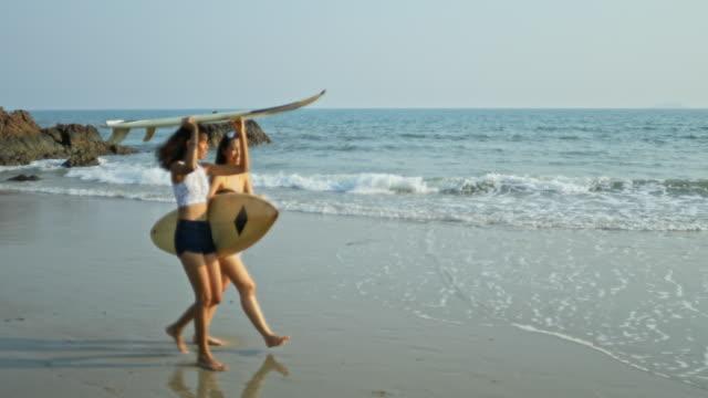 美しい若い女性が浜辺を歩いている。 - 水着点の映像素材/bロール