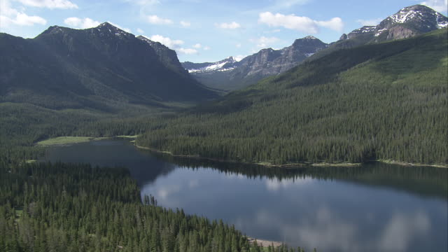stockvideo's en b-roll-footage met beautifully wooded mountains encompass deep lake filled valleys in yellowstone national park. available in hd. - yellowstone national park