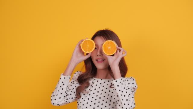 vídeos de stock e filmes b-roll de beauty asia woman with orange fruit - cor isolada