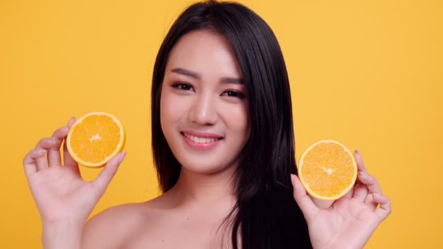 vidéos et rushes de femme d'asie de beauté avec le fruit orange - touche de couleur