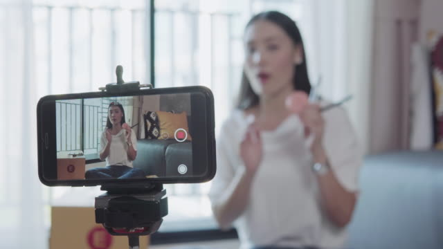 beauty blogger demonstrating how to make up and review products on live broadcast use smartphone, life of an influencer - live broadcast stock videos & royalty-free footage