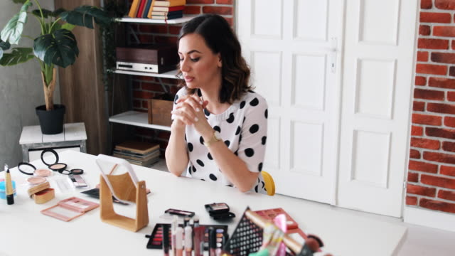 beauty blogger present beauty cosmetics sitting in front camera for recording video. happy beautiful young woman use cosmetics review make up tutorial broadcast live video to social network. - live broadcast stock videos & royalty-free footage