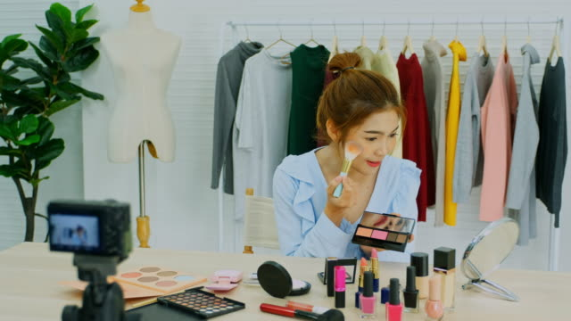 beauty blogger, vlog showing cosmetics sitting in front of camera while recording video, happy beautiful young asian woman influencer broadcast how to make  to social network - tutorial stock videos and b-roll footage