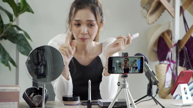 beauty blogger woman filming daily makeup routine tutorial on camera. - examining stock videos & royalty-free footage