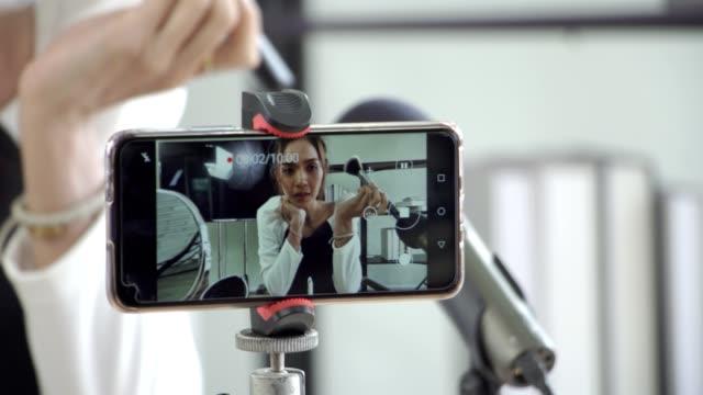 stockvideo's en b-roll-footage met de bloggervrouw die van de schoonheid dagelijkse make-uproutinetutorial op camera filmt. - merchandise