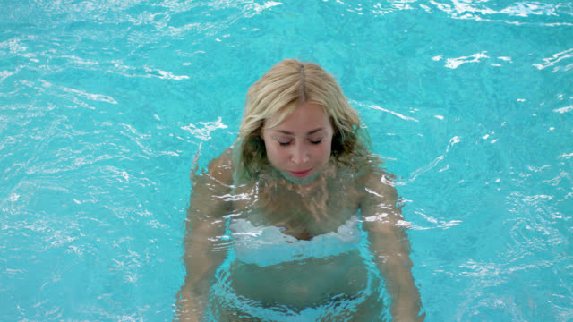 beauty day spa indoor pool – sensual beautiful woman with long blonde hair sparkling eyes in her late 30s wearing white bikini – looking at camera with dry hair and slowly submerging into the water, emerging up again with wet hair, looking at camera again - wet hair stock videos and b-roll footage