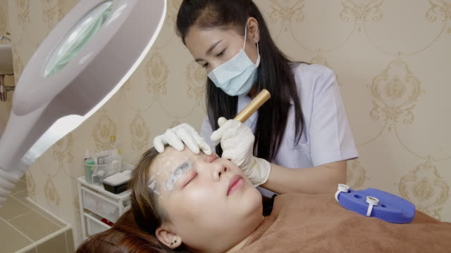 beauty expert in the face, doing the eyebrow tattoo on the customer's face. - beauty treatment stock videos & royalty-free footage