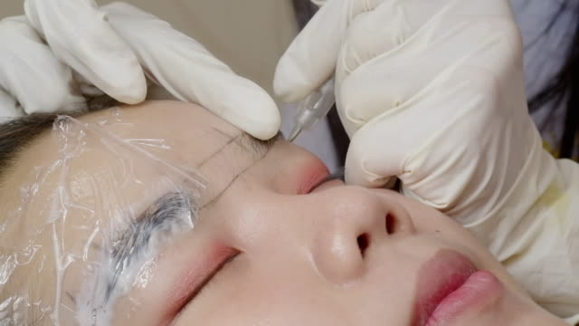 beauty expert in the face, doing the eyebrow tattoo on the customer's face. - eyebrow stock videos & royalty-free footage