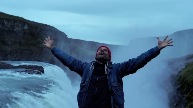 vídeos de stock, filmes e b-roll de beleza da natureza. cachoeira admirando viajante. braços abertos - mãos estendidas